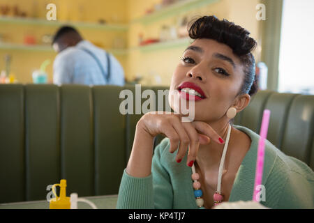 Portrait of young woman putting her chin on fist looking into camera at restaurant