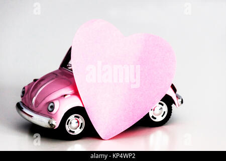 Pink heart on pink toy car - Stock Photo