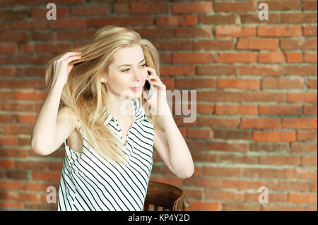 A blonde girl is calling by the phone against a brick wall background, calling the apartment repair service. Advertising - Stock Photo