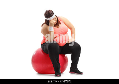 Sad overweight woman sitting on an exercise ball isolated on white background - Stock Photo