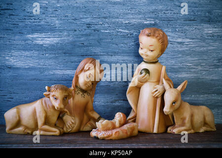 the holy family, the Child Jesus, the Virgin Mary and Saint Joseph, on a wooden surface, against a gray rustic wooden - Stock Photo