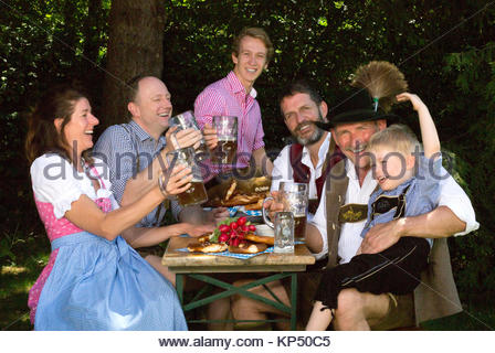 bavarian family sitting outside on a bench and drinking beer - Stock Photo