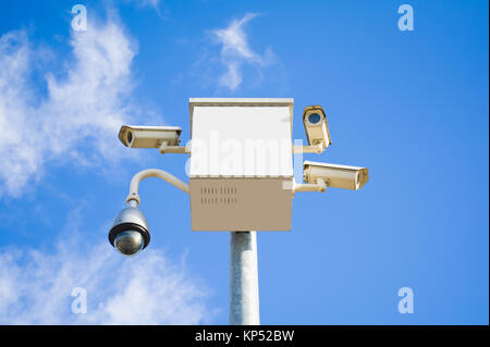 four outside security cameras cover multiple angles on blue sky - Stock Photo