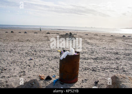 Overflowing rusty bin full of rubbish, waste on the beach, Dollymount Strand, Dublin Ireland, plastic pollution - Stock Photo