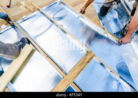 Cutting of zinc plates to cover a roof in Paris, France. - Stock Photo