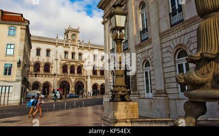 At right National Theatre Dona Maria II, on background Main entrance, Rossio Railway Station, Estação de Caminhos - Stock Photo