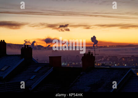 Smoke from Port Talbot Steel Works is visible in the horizon, seen over roof tops during an early frosty morning - Stock Photo