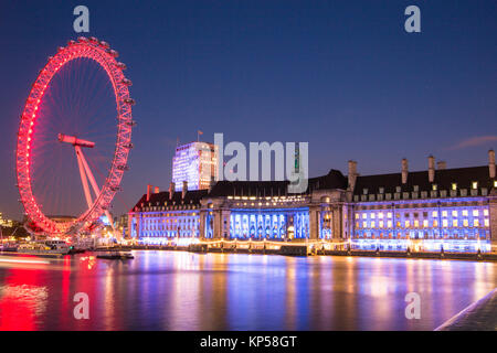 Famous London Landmark, the London Eye and London Aquarium, illuminated at night - Stock Photo