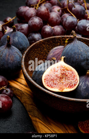 Ripe Grapes and Figs on dark concrete background - Stock Photo