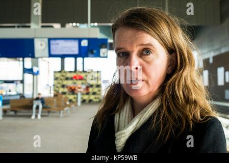 Breda, Netherlands. Mid adult caucasian woman waiting at the Railway Station's Platform 3 for her connecting train - Stock Photo