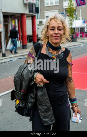 Tilburg, Netherlands. Mature adult caucasian woman strolling the annual fairgrounds during morning hours - Stock Photo