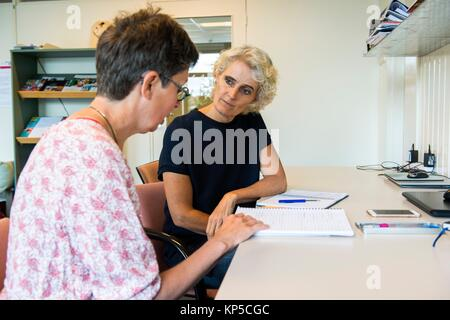 Tilburg, Netherlands. Mature adult woman having a coaching interview while searching for a new job and occupation. - Stock Photo