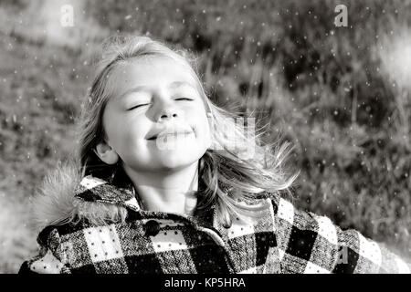 beautiful young girl standing in open field as snow begins to fall in wintertime - Stock Photo