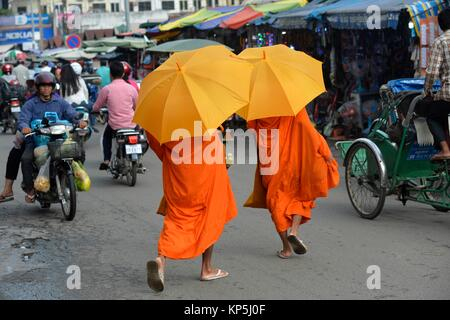 Buddhist monks receiving early morning food alms in Phnom Penh,Cambodia,Indochina,Southeast Asia,Asia. - Stock Photo