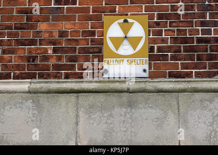 fallout shelter sign on brick building background - Stock Photo