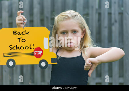 adorable school age girl frowning and holding first day of school sign - Stock Photo