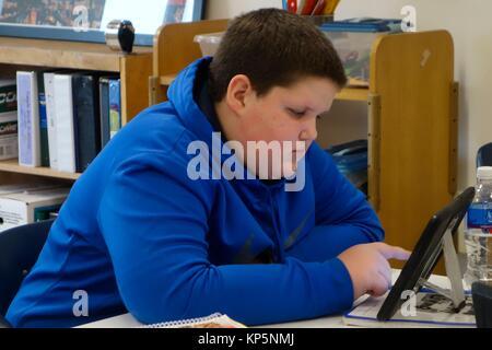 Preteen Boy Using iPad in Classroom, Wellsville, New York, USA. - Stock Photo