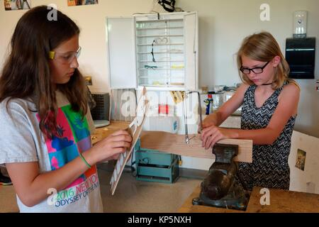 6th Grade Girls Using Coping Saw With Vice in Technology Class, Wellsville, New York, USA. - Stock Photo