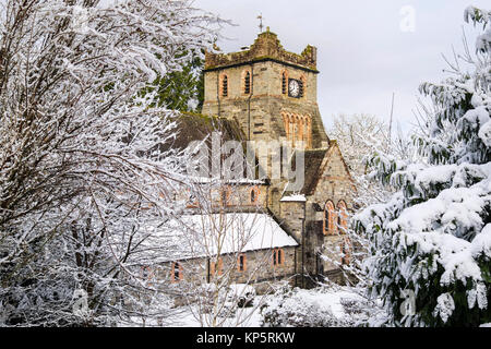 St Mary's Parish church with snow laden branches of trees in Welsh village in winter 2017. Betws-y-Coed, Conwy valley, - Stock Photo