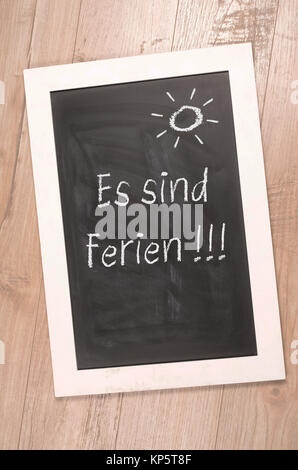 Chalkboard with the German word vacation on a rustic wooden background - Stock Photo