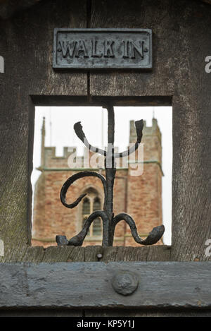 view through the opening in an old wooden garden door with the tower of the church of St George, Dunster, Somerset, - Stock Photo