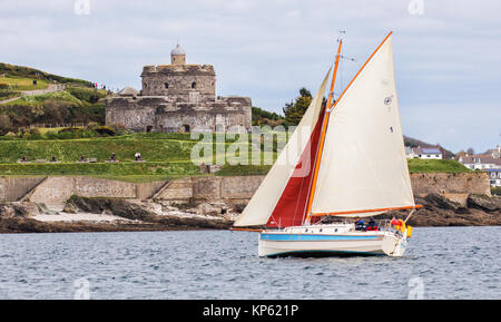 Small yacht with red and white sails passing St Mawes Castle on the Roseland peninsula in Cornwall UK - Stock Photo