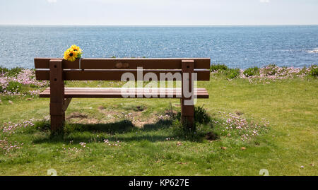 Empty wooden bench overlooking the English Channel with poignant memorial flowers on the coastal footpath of Portland - Stock Photo