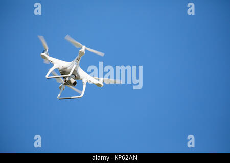 White photography drone in flight against a clear blue sky - Stock Photo