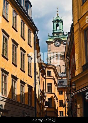 A narrow street in Stockholm with the clock tower of the Church of St. Nicholas (Sankt Nikolai kyrka) also known - Stock Photo