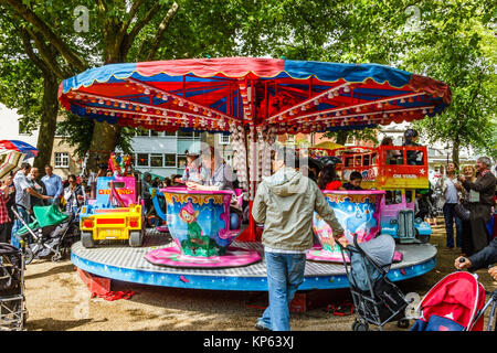 Children's carousel at the Fair in the Square, Pond Square, Highgate, London, UK - Stock Photo
