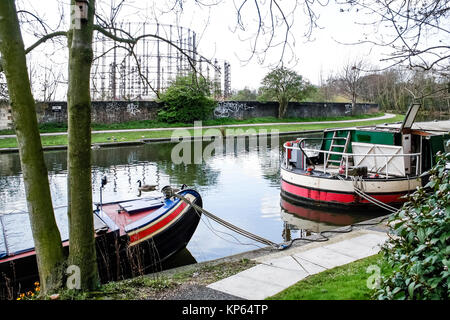 Narrowboats on Regent's Canal at Kensal Green, London, UK,  the disused gasometers in the background - Stock Photo