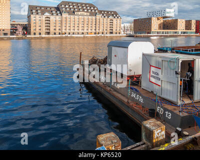 Pontoon of a mobile industrial diver station on the west bank of the Spree in the foreground opposite the east bank - Stock Photo