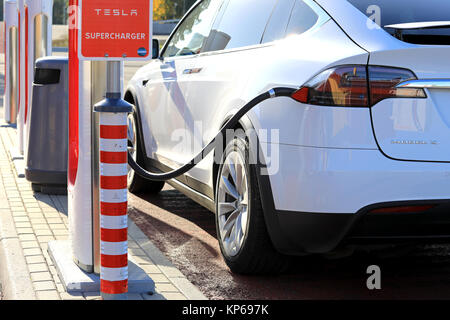 TOIJALA, FINLAND - SEPTEMBER 24, 2017: Close up of new Tesla Model  X electric suv plugged in at Supercharger station. - Stock Photo