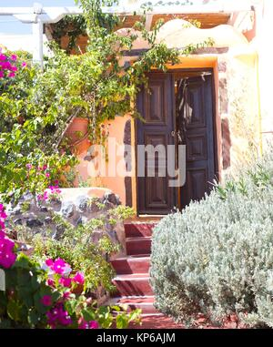 Beautiful solid brown door with stairs and flowers all around. Typical house entrance of the village of Pyros. Pyrgos - Stock Photo