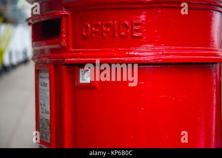 Classic red round mailbox stand in streets of London, England on a clear no rainy day. - Stock Photo