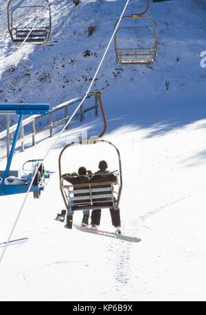 A chairlift and skiers on piste in Gatlinburg, in the region of Teneesee, in the USA. - Stock Photo