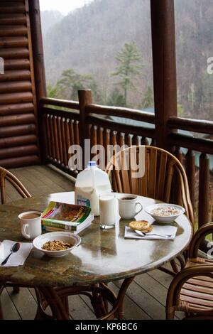Breakfast table set with milk and cereals on the wooded balcony of a ski resort. The view from the mountains is - Stock Photo