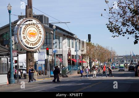 People stroll at Fishermans's Wharf in San Francisco, California. Famous Fisherman Wharf circular sign in the famous - Stock Photo