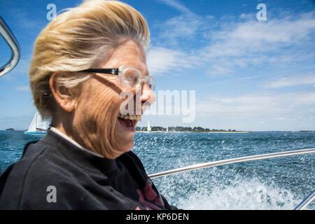 Caucasian retired senior, mature woman having fun and laughing during an outing on the boat in the ocean, in Brittany, - Stock Photo