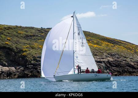 Sail boat with full sail and full wind passing by in the French ocean and on the coast of Bretagne, Brittany, France - Stock Photo