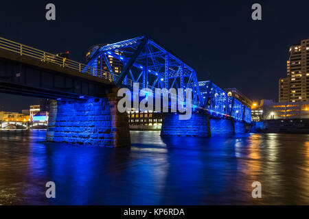 Blue Bridge at night, reflecting off the Grand River in Grand Rapids, Michigan, USA - Stock Photo