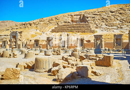 Discover Persepolis archaeological site with its ancient landmarks - tomb on the mountain slope and Hundred Columns - Stock Photo