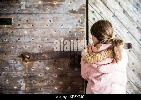Close up of a Preteen caucasian girl trying to push an old wood heavy door in an old Fort. Fort Macon State Park, - Stock Photo