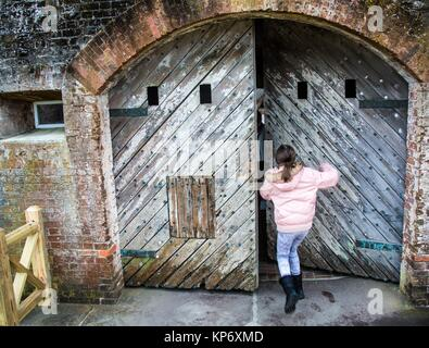Preteen caucasian girl trying to push an old wood heavy door in an old Fort. Fort Macon State Park, originally called, - Stock Photo