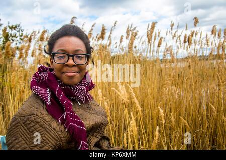 African American teenager girl dressed warm laughing and making a proud face in front of a wheat field at the palace, - Stock Photo