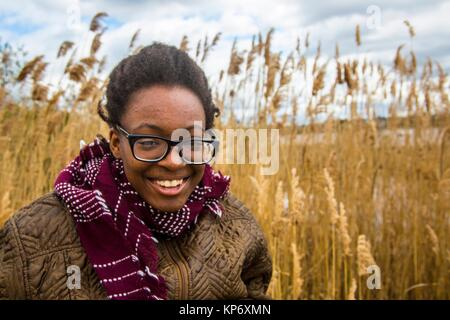 African American teenager girl dressed warm and laughing in front of a wheat field at the  Tryon Palace, New Bern, - Stock Photo