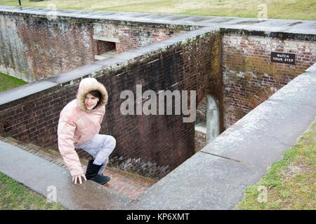 Preteen girl with a big sweater pink winter jacket with a feather hood looking at going down the stairs in an old - Stock Photo