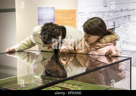 Handsome caucasian dark hair father looking through a display window with his preteen daughter in a museum at an - Stock Photo