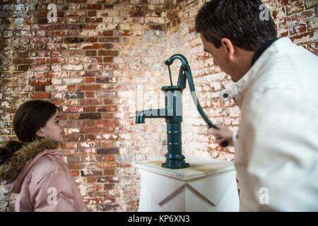 Handsome caucasian dark hair man in his 40's 50's pumping an old cast iron fountain and his daughter drinking out - Stock Photo