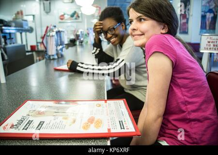 Pre-teen and teen in a diner laughing and reading a menu, eating, having a fun girls times, drinking a milkshake - Stock Photo